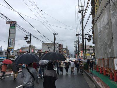 北口の大通りを傘を差して歩く
